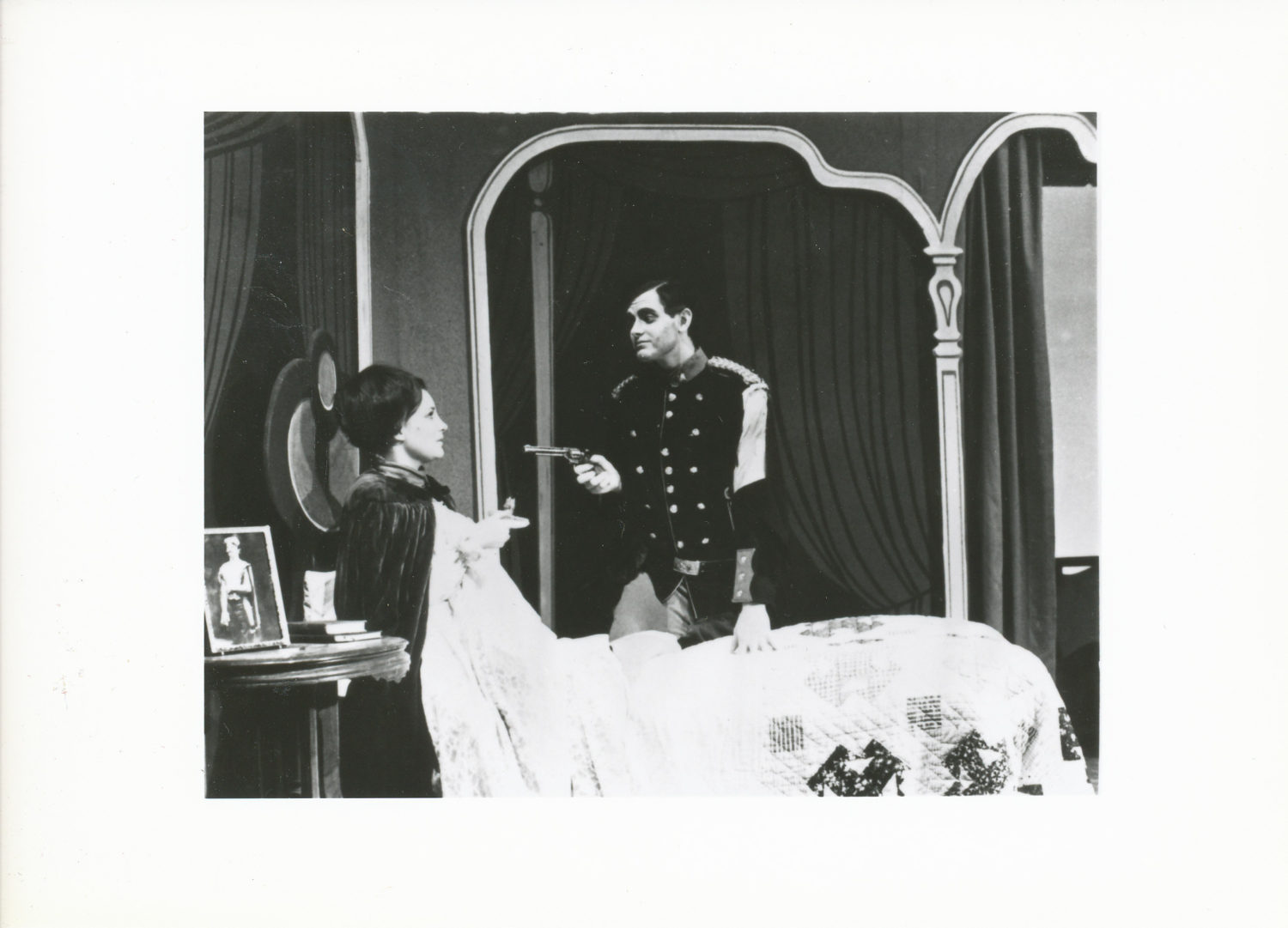 Parnell Hall as Captain Bluntschli holds Wendy Nute as Raina at gunpoint in a summer stock production of Arms and the Man.